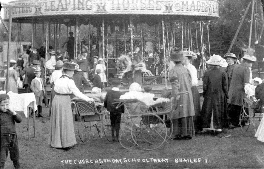 Lower Brailes Sunday School Treat, showing family groups, perambulators and roundabout (Electric Leaping Horses) in use.  1900s |  IMAGE LOCATION: (Warwickshire County Record Office)