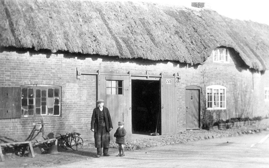 Cottage, possibly attached to smithy, Clifton upon Dunsmore.  1920s  [The photograph shows Mr Lloydall (blacksmith) and his son outside the smithy in Clifton upon Dunsmore.] |  IMAGE LOCATION: (Warwickshire County Record Office)