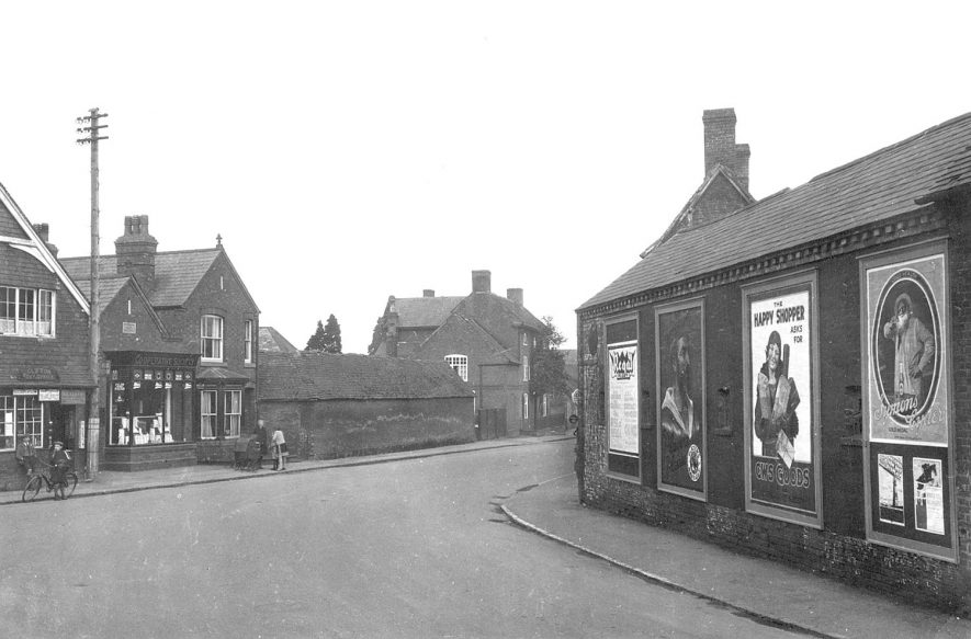 Probably Market Harborough Road, Clifton upon Dunsmore.  1920s [The first shop on the left was the Post Office. The brick wall on the left was part of Allans Farm. The chimney rising behind the hoardings on the right are those of the Bull Inn. It has been suggested the photographer stood on the road with his back to the Church in Church St looking around the corner to Main St.] |  IMAGE LOCATION: (Warwickshire County Record Office)