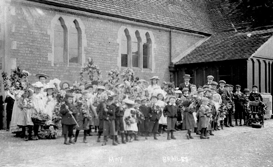 Brailes School pupils outside school, dressed as sweeps, flower girls etc and carrying floral decorations in readiness for May day celebrations. Teachers in charge.  1900s    IMAGE LOCATION: (Warwickshire County Record Office)