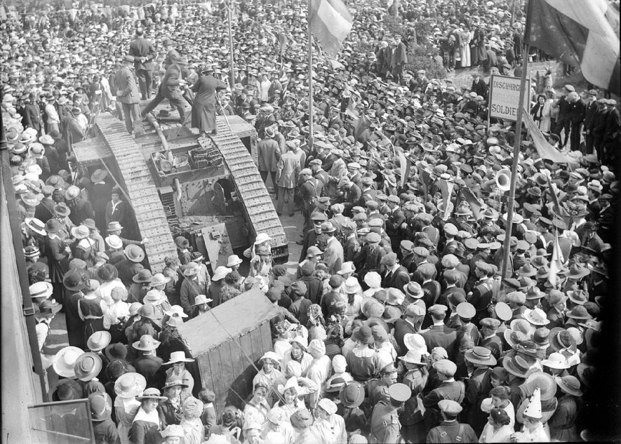 A large crowd around an old British tank, in Alcester, with perhaps a band and placards about discharged sailors and soldiers, possibly armistice celebrations in 1918.[Looking closely at the door at the rear of the tank's sponson it is possible to make out a boy scout. Boy Scouts were used to act as 'doormen' when tanks were used to sell War Bonds, an office being set up in the tank. This strongly suggests this is part of Alcester's tank week. The photograph shows the crowd wearing summery clothes which indicates that is unlikely to be an Armistice celebration.] |  IMAGE LOCATION: (Warwickshire County Record Office)