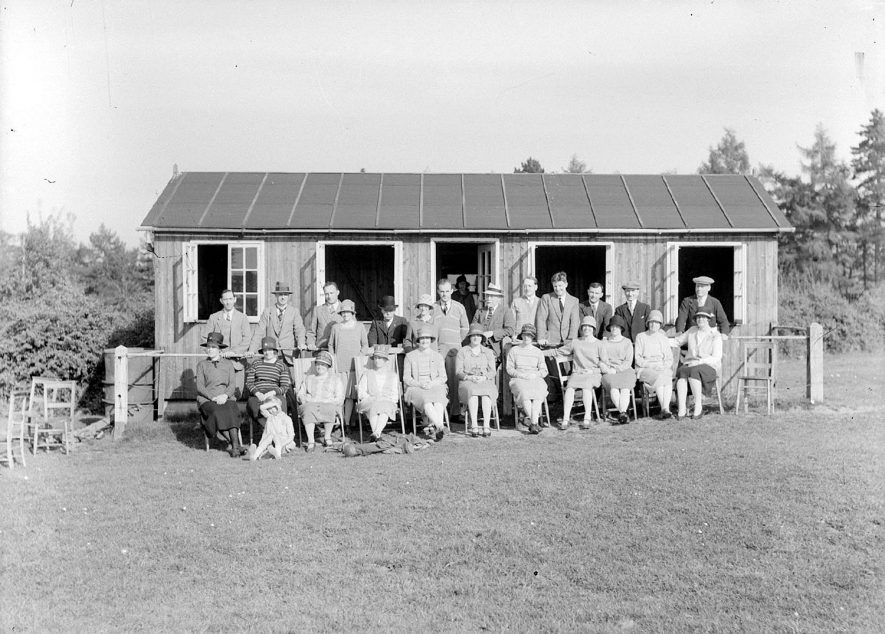 A group of people outside a hut in or around Alcester.  There is a golf bag in the foreground.  These could be golfers outside the clubhouse however no golf club now exists in Alcester.  1930s |  IMAGE LOCATION: (Warwickshire County Record Office)