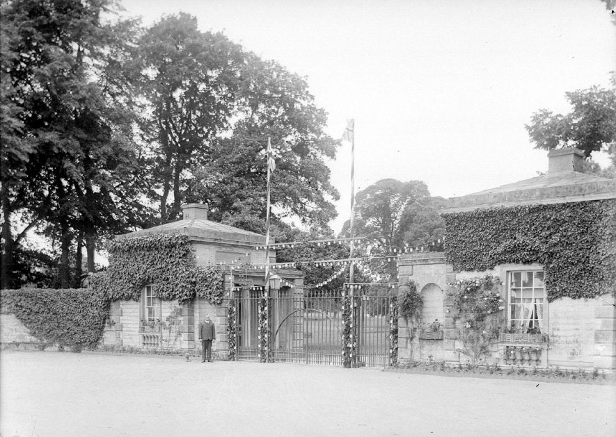 Lodges and gates to Ragley Hall which have been decorated for some occasion. Arrow.  1930s |  IMAGE LOCATION: (Warwickshire County Record Office)