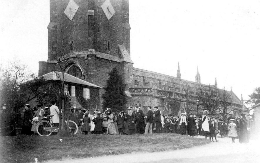 Brailes Church showing part of the tower and clock faces with a crowd of people outside, the reason for the crowd is unknown.  1900s |  IMAGE LOCATION: (Warwickshire County Record Office)