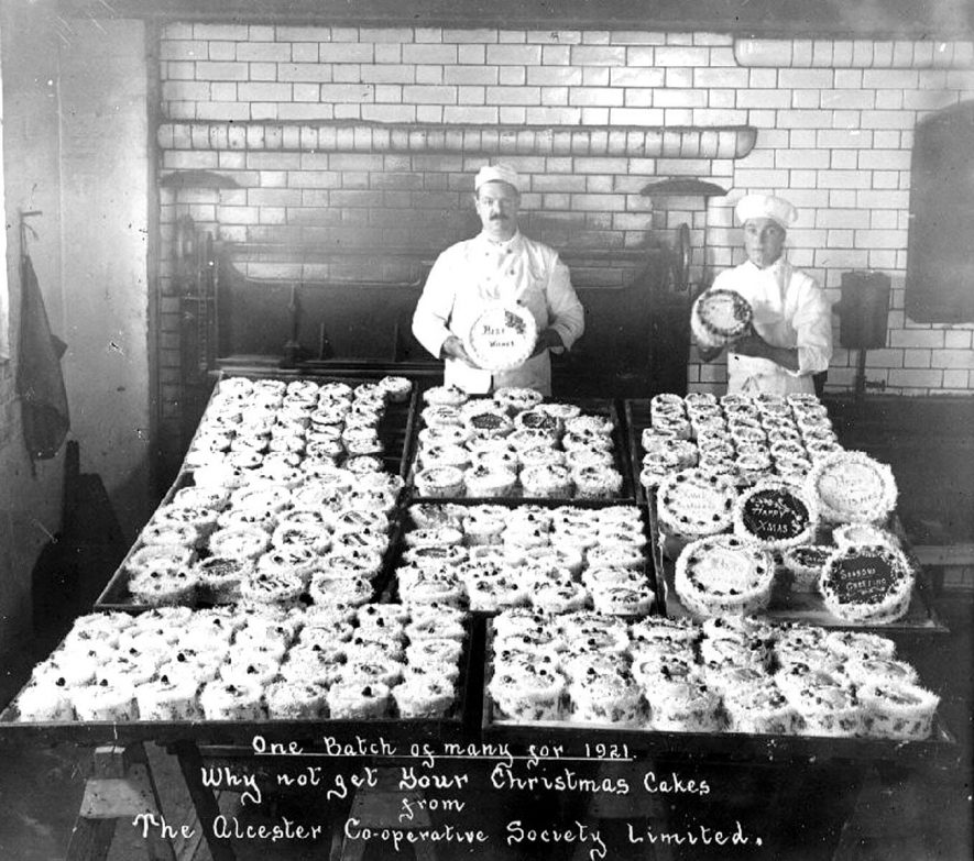 Two bakers from Alcester Co-op with a display of Christmas cakes.  1921 |  IMAGE LOCATION: (Warwickshire County Record Office)