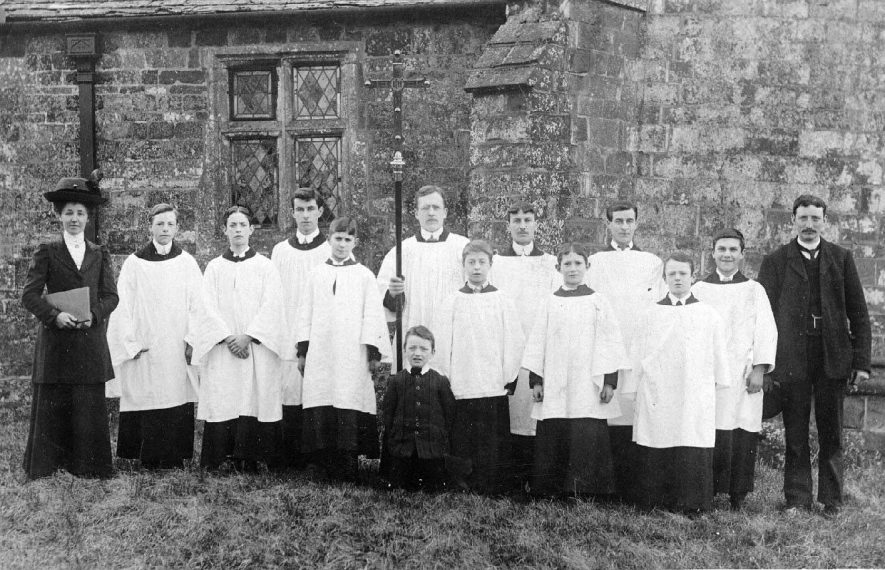 Group of choristers with Cross standing outside Lower Brailes Church.  1900s |  IMAGE LOCATION: (Warwickshire County Record Office)