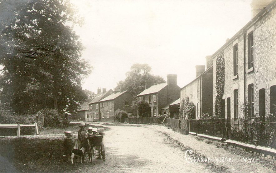 Village street with group of children and perambulator in the foreground, Grandborough.  1920s |  IMAGE LOCATION: (Warwickshire County Record Office)