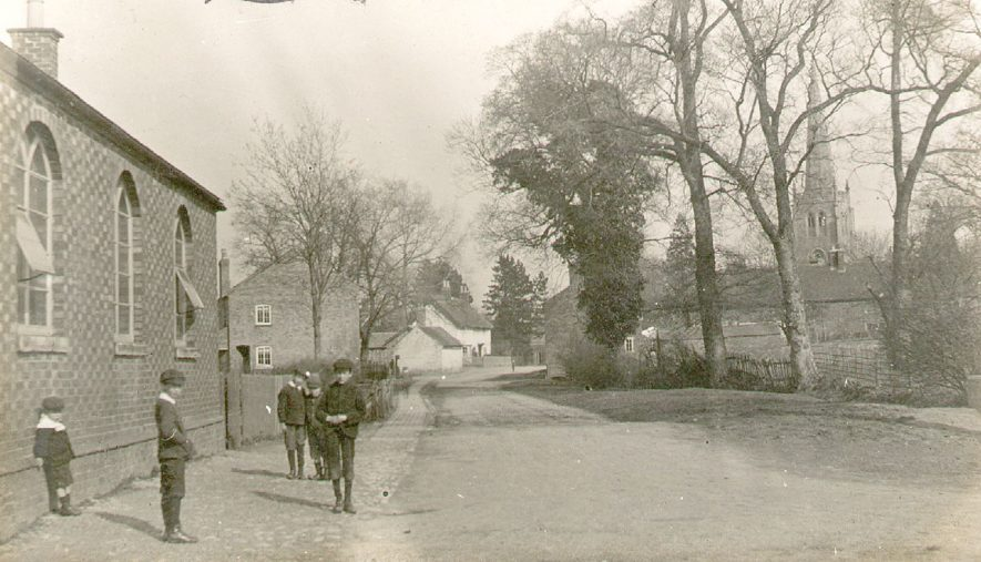 Children outside what is possibly the school in Grandborough. The church is seen through the trees in the distance. 1900s[The first building on the left is what is now Virginia Cottage and the white building in the background was the George Pub][Confirmation received that this is Grandborough School] |  IMAGE LOCATION: (Warwickshire County Record Office)