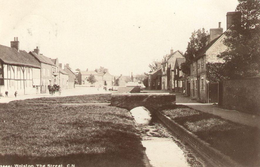 The Street, Wolston, with small stream running under footbridge and houses to either side. A horse and carriage is also shown.  1900s |  IMAGE LOCATION: (Warwickshire County Record Office)