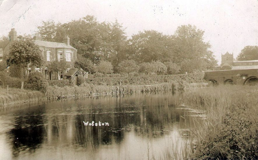 A detached house on the banks of the River Avon with a bridge and the church in the background, Wolston.  1910s |  IMAGE LOCATION: (Warwickshire County Record Office)