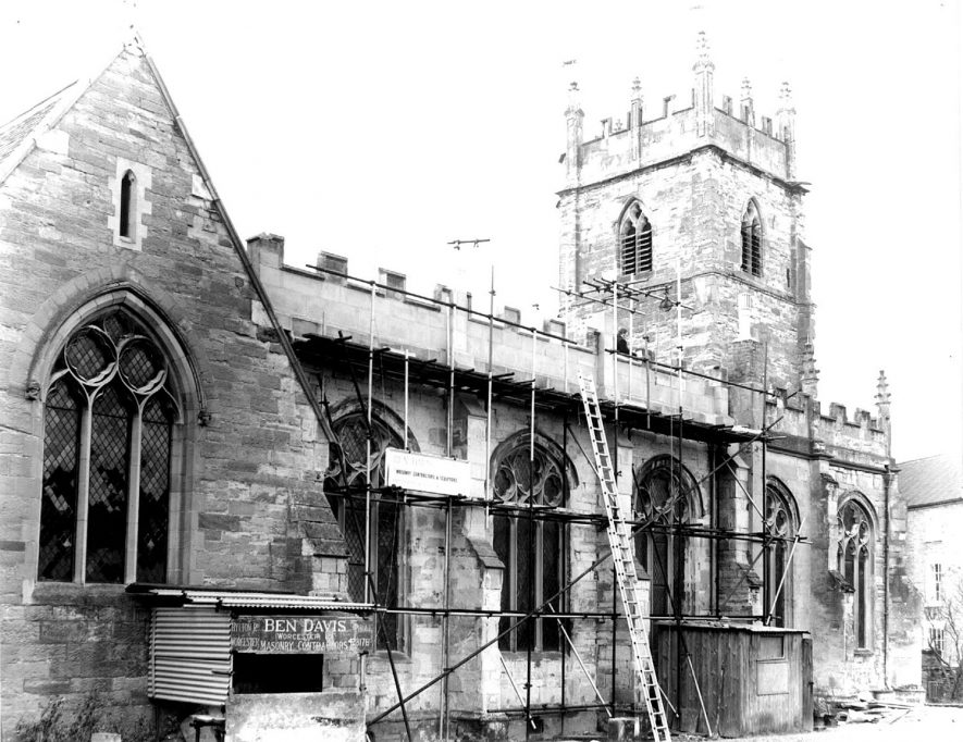 Exterior of Alcester parish church with scaffolding.  The masonry contractor's board reads 'Ben Davis'.  1960s |  IMAGE LOCATION: (Warwickshire County Record Office)