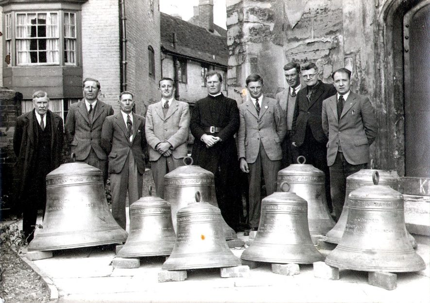 A ring of eight bells on the ground outside Alcester parish church with the Vicar and group of men behind them.  1948 |  IMAGE LOCATION: (Warwickshire County Record Office)