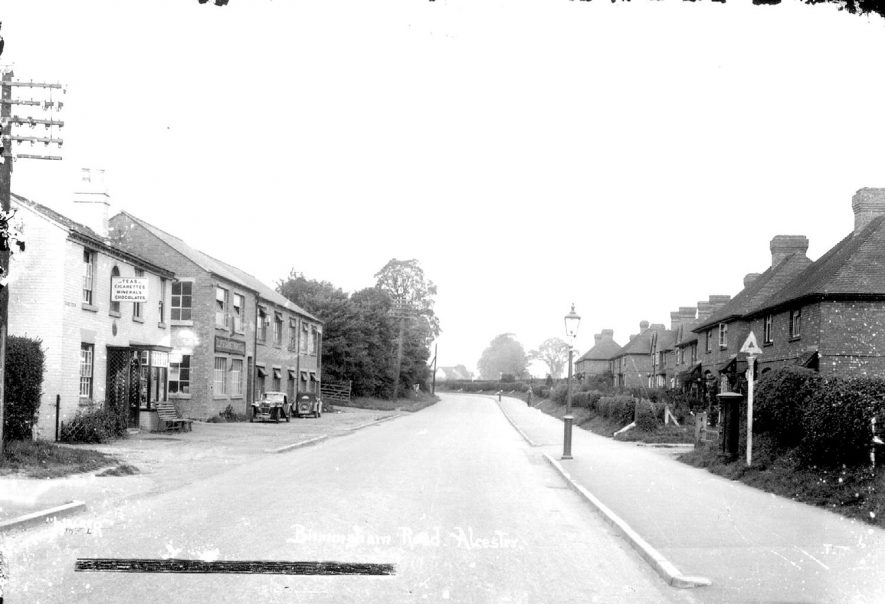 Birmingham Road, Alcester, lined with shops and houses and with two parked cars.  1930s |  IMAGE LOCATION: (Warwickshire County Record Office)