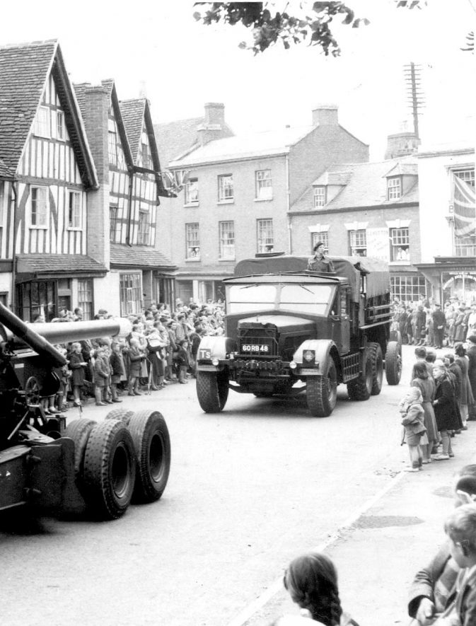 Victory parade of military vehicles with onlookers on pavements, Alcester.  1940s |  IMAGE LOCATION: (Warwickshire County Record Office)