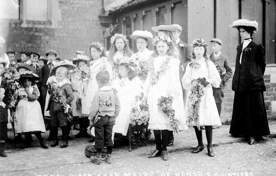 May Queen, maids of honour & courtiers, holding May wands, standing in group outside school with teacher, Lower Brailes.  1900s |  IMAGE LOCATION: (Warwickshire County Record Office)
