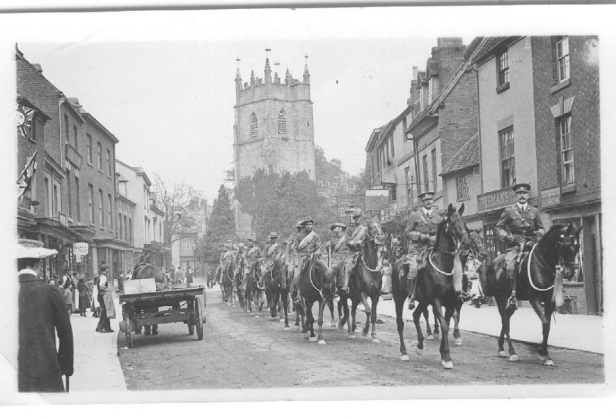 Military parade of soldiers and horses in Alcester High Street with the church in the background.  1900s |  IMAGE LOCATION: (Warwickshire County Record Office)
