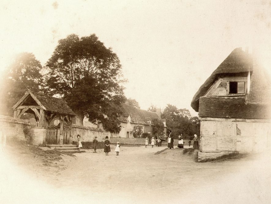 View of Welford on Avon, with lych gate on the left and children and adults standing in the road.  1900s    IMAGE LOCATION: (Warwickshire County Record Office)