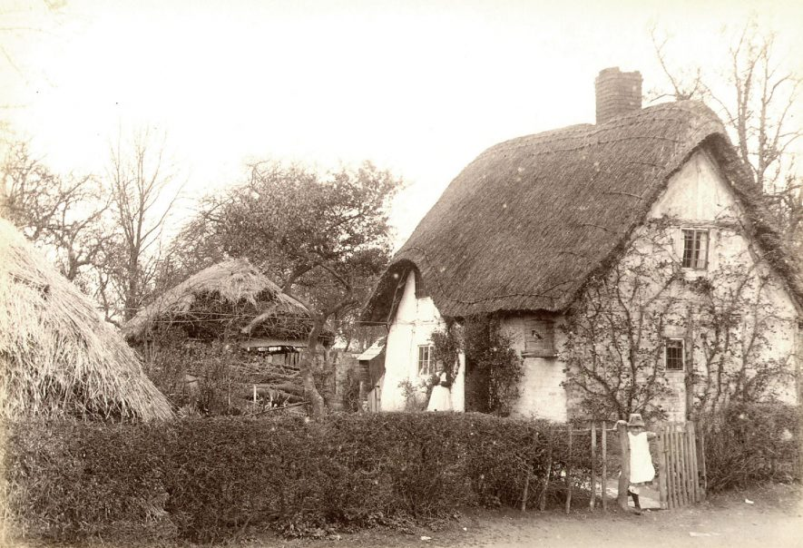 Small thatched and timbered cottage in Welford on Avon.  A child is standing at the gate and a lady at the door. Note the caged bird on the wall.  1890s |  IMAGE LOCATION: (Warwickshire County Record Office)