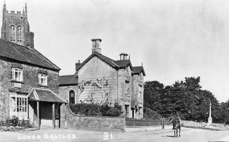 Houses in front of Lower Brailes Church, butcher's shop on the left, child riding a horse on the road and the  War Memorial in the background.  1910s |  IMAGE LOCATION: (Warwickshire County Record Office)