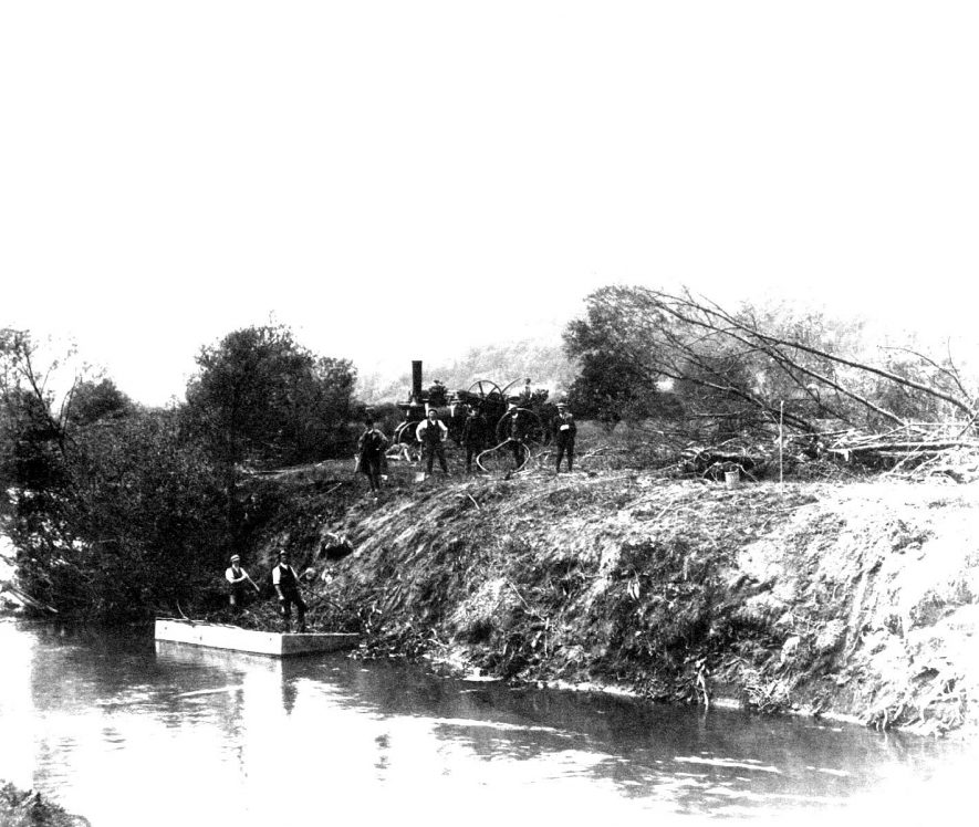 A Bomford and Evershed agricultural steam engine and farmworkers on the side of the river, Salford Priors.  1900s |  IMAGE LOCATION: (Warwickshire County Record Office)