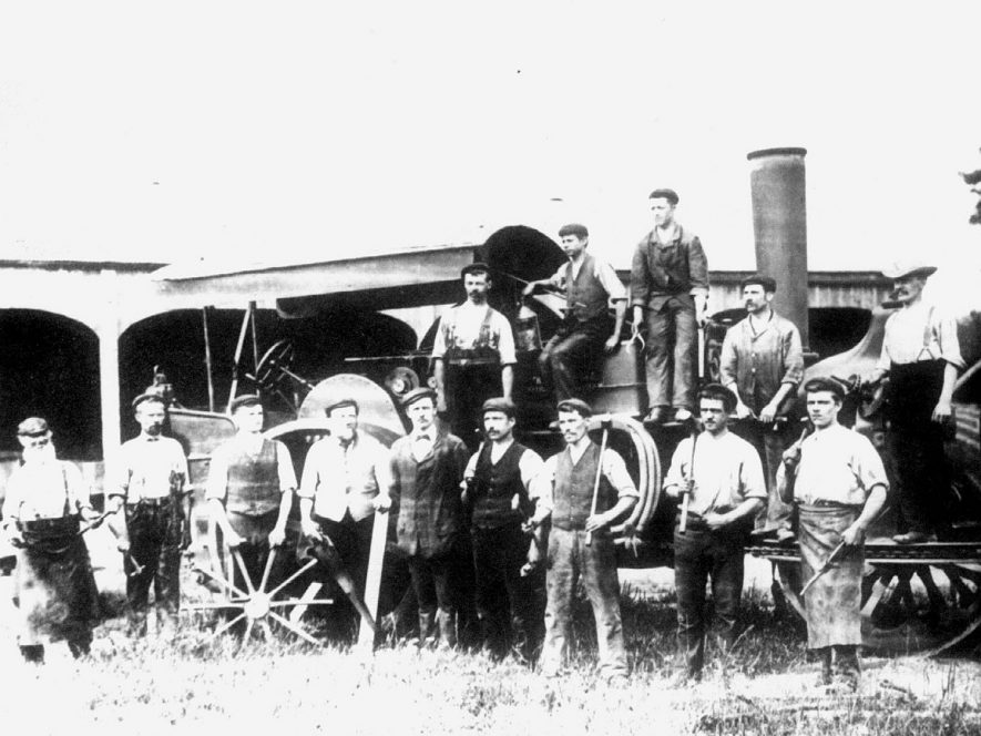 A group of Bomford and Evershed agricultural engineering workers in front of a steam engine, Salford Priors.  1900s |  IMAGE LOCATION: (Warwickshire County Record Office)
