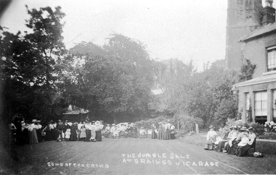 The vicarage garden during a jumble sale showing a large crowd of people, Lower Brailes.  1900s |  IMAGE LOCATION: (Warwickshire County Record Office)