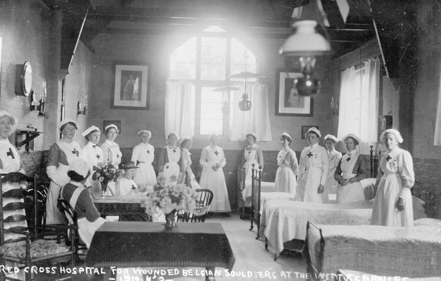 Interior of The Institute which was in use as a hospital for wounded Belgian Soldiers run by the Red Cross, showing the interior of a ward with a group of nurses. Note the paraffin lamp lighting.  Lower Brailes.  1914. |  IMAGE LOCATION: (Warwickshire County Record Office)