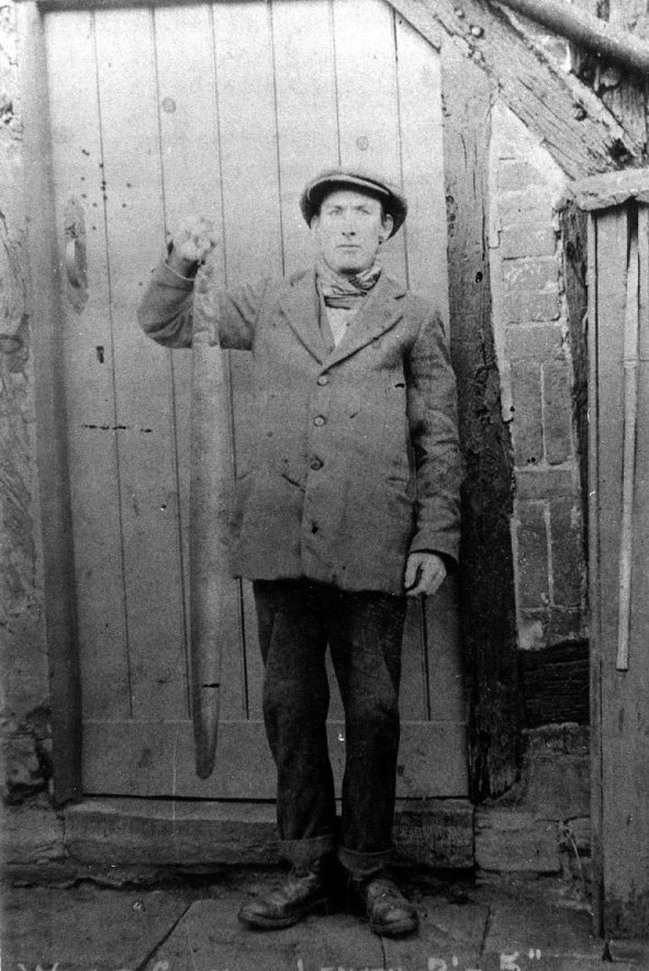 William King, a deaf and dumb man, holding a giant eel caught at Broom.  1900s |  IMAGE LOCATION: (Warwickshire County Record Office) PEOPLE IN PHOTO: King as a surname, King, William