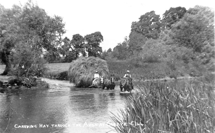 A load of hay being pulled through the River Avon by horses, near to Salford Priors.  1920s |  IMAGE LOCATION: (Warwickshire County Record Office)