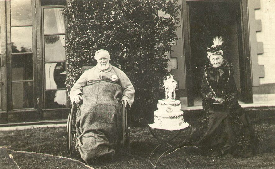 The Rev. and Mrs B Stannus of Arrow. The Reverend is seated in a wheelchair and there is a decorated cake standing between them.  Circa 1900 |  IMAGE LOCATION: (Warwickshire County Record Office) PEOPLE IN PHOTO: Stannus, Revd B