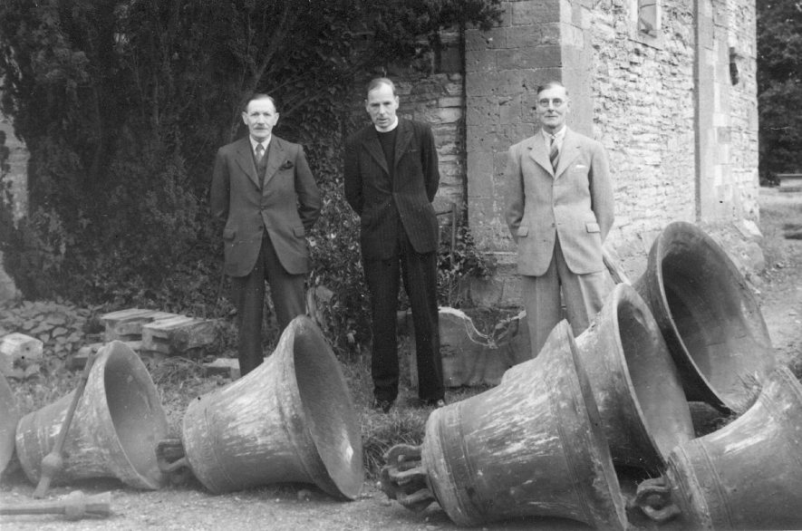 Three men, one the vicar, standing behind six church bells which are laying on the ground. Salford Priors.  1940s    IMAGE LOCATION: (Warwickshire County Record Office)