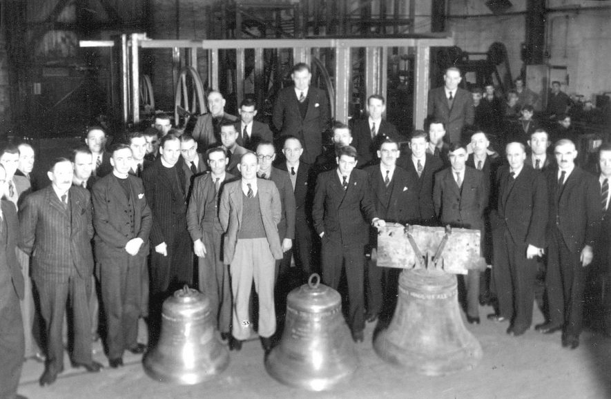 A group of men including the vicar standing behind three new church bells at Salford Priors.  1940s |  IMAGE LOCATION: (Warwickshire County Record Office)