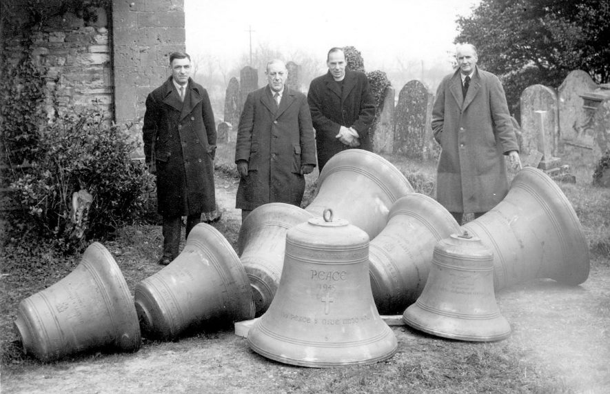 Four men, one of whom is the vicar, standing behind eight new church bells at Salford Priors.  1940s |  IMAGE LOCATION: (Warwickshire County Record Office) SCAN DATE: (1966)
