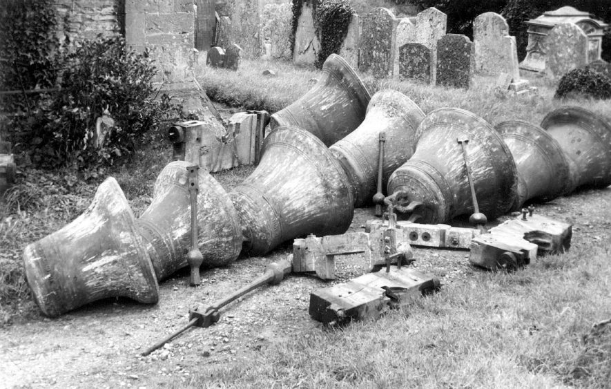 Eight church bells laying on the ground in the churchyard at Salford Priors.  1940s |  IMAGE LOCATION: (Warwickshire County Record Office)