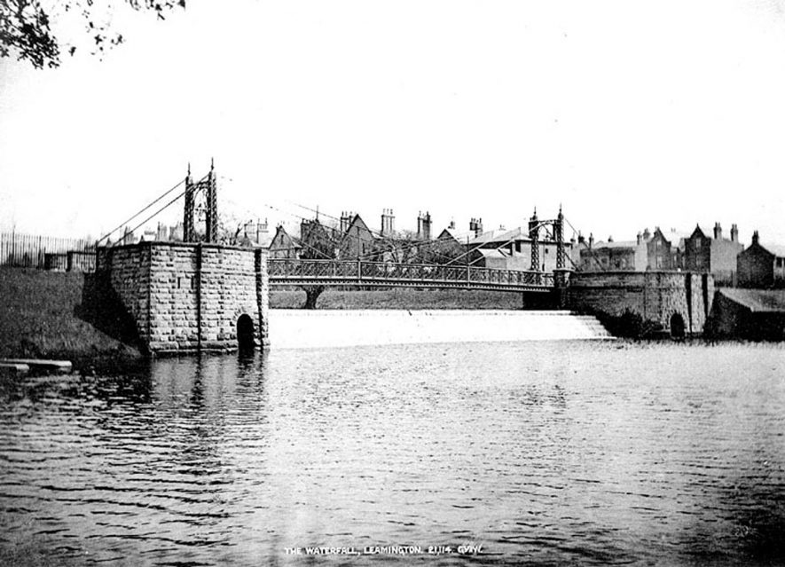 Weir and footbridge spanning the River Leam, Leamington Spa.  1900s |  IMAGE LOCATION: (Warwickshire County Record Office)