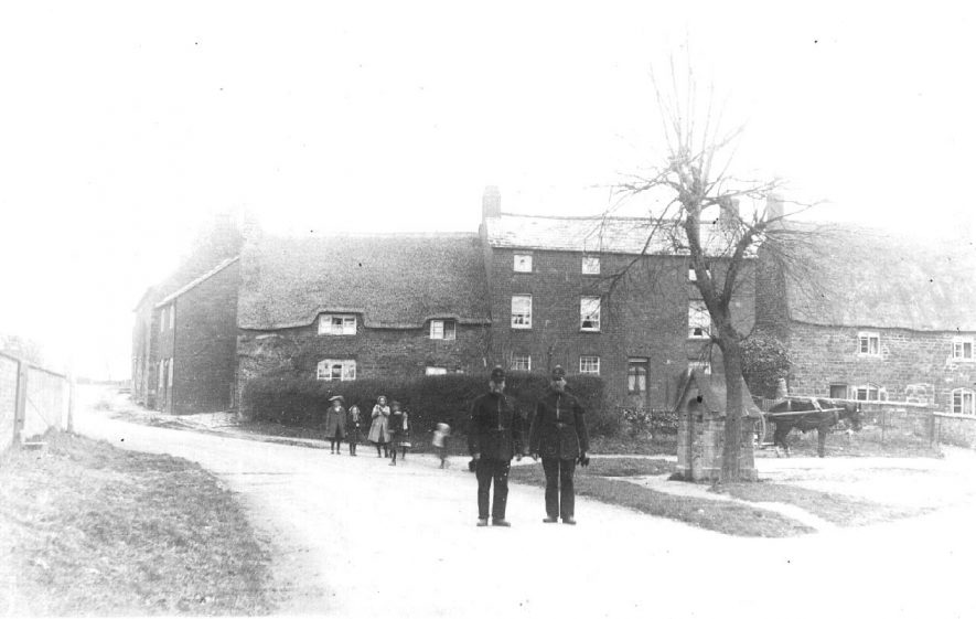 Street  junction at Upper Brailes. Water fountain in brick shelter, horse and cart and two policemen.  1900s |  IMAGE LOCATION: (Warwickshire County Record Office)