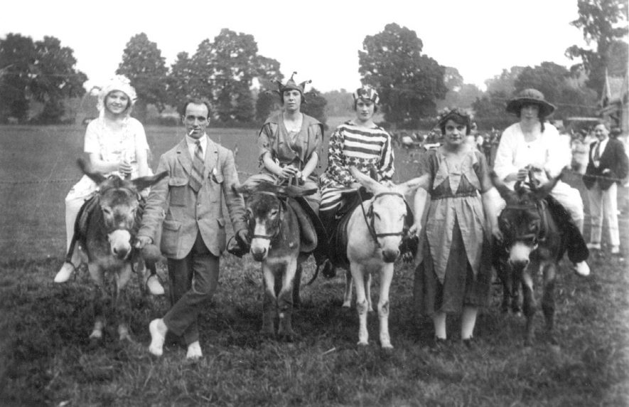 A group of people riding donkeys in Ashorne.  1920s |  IMAGE LOCATION: (Warwickshire County Record Office)