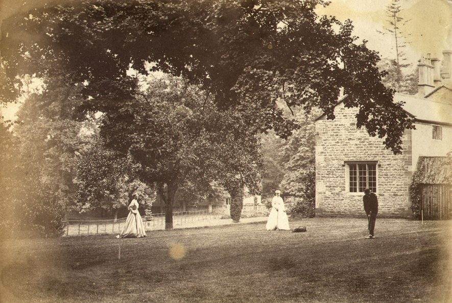Cherington House and gardens with a man and two ladies playing croquet.  1880/90s |  IMAGE LOCATION: (Warwickshire County Record Office)