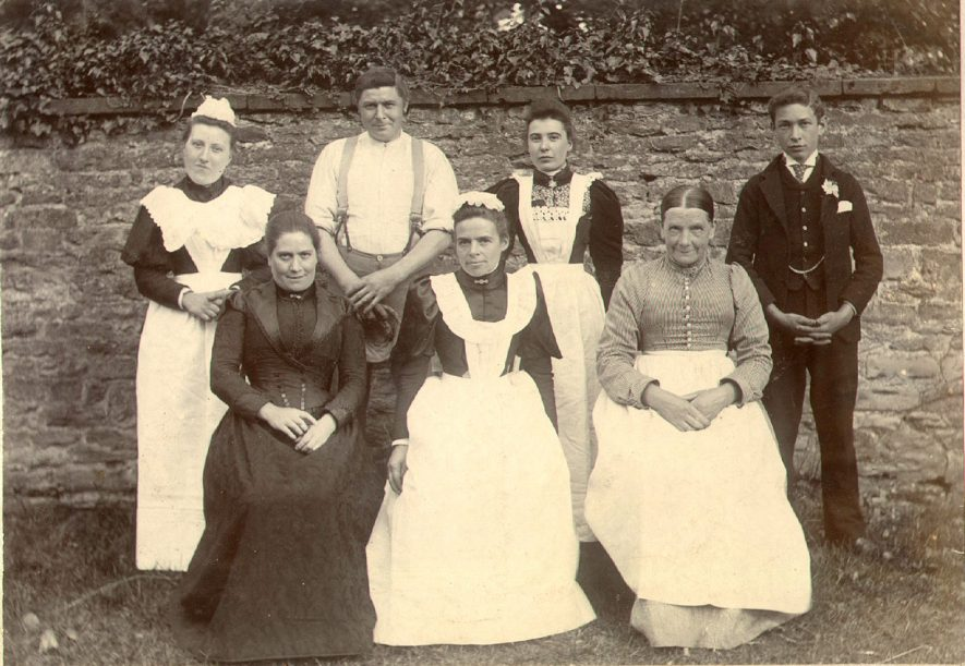 Group of family servants with Mrs Dickins of Cherington House. 1895Back row from left - Elizabeth Sturch, H. Woodward, L. Cooper and T. Lewingdon.Front row from left - Mrs Woodward, E. Sexston and Mrs Brooks. |  IMAGE LOCATION: (Warwickshire County Record Office) PEOPLE IN PHOTO: Sturch, Elizabeth, Sturch as a surname, Sexston, E, Sexston as a surname, Lewingdon, T, Lewingdon as a surname, Dickins, Mrs, Dickins as a surname, Cooper, L, Cooper as a surname, Brooks, Mrs, Brooks as a surname