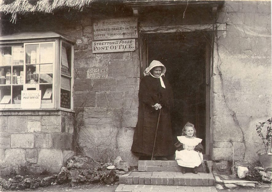 An old lady, believed to be Judith Wells and little girl outside the post office at Stretton on Fosse.Judith Wells (nee Keen) was the mother of Margaret Wells, the wife of James William Edgington who ran the Post Office. His name appears on the board to the left of the doorway.  1890s |  IMAGE LOCATION: (Warwickshire County Record Office)