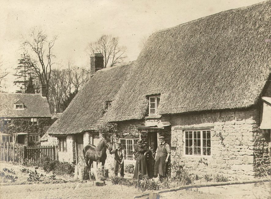 People and horse standing outside thatched cottages in Cherington.  1900s |  IMAGE LOCATION: (Warwickshire County Record Office)