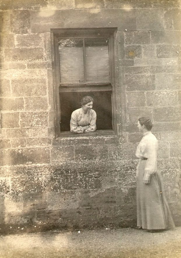 Two women chatting, one leaning out of a window, the other standing outside. Cherington.  1900s |  IMAGE LOCATION: (Warwickshire County Record Office)