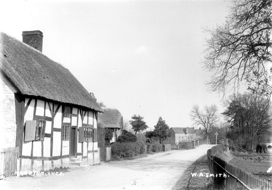 Thatched timbered cottage in Hampton Lucy. The mill and bridge over the River Avon is seen in the background.  1900s |  IMAGE LOCATION: (Warwickshire County Record Office)