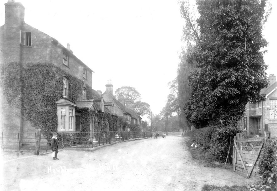 Village street in Hampton on the Hill. A small boy is standing in the foreground.  1900s |  IMAGE LOCATION: (Warwickshire County Record Office)