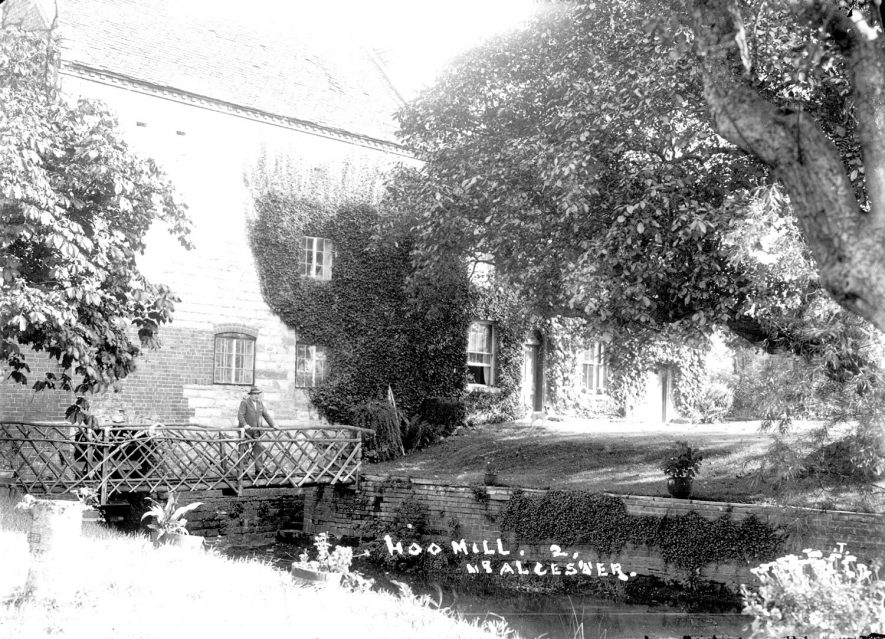 Hoo Mill, Alcester.  A man is standing on a rustic footbridge in front of the mill.  1930s [The man's name is Albert Stewart who lived at the mill at the time] |  IMAGE LOCATION: (Warwickshire County Record Office)