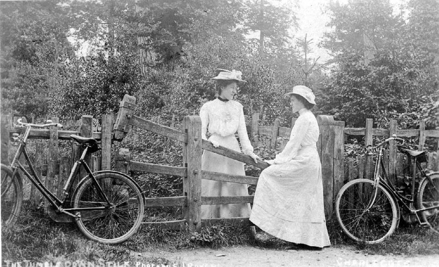 Two ladies with their bicycles standing at the Tumbledown Stile, Charlecote.  1900s |  IMAGE LOCATION: (Warwickshire County Record Office)