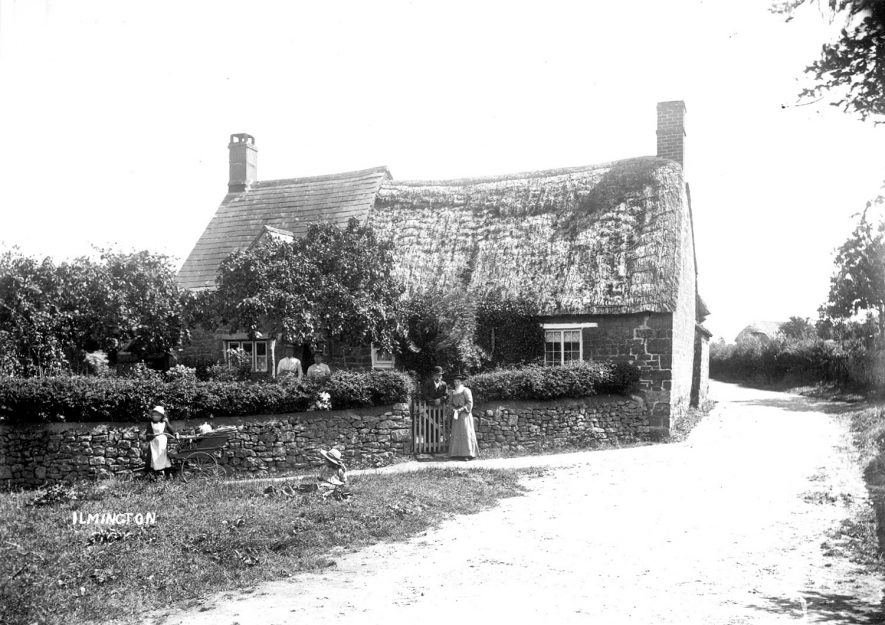 Thatched cottage, with woman and children at gate, Ilmington.  1900s    IMAGE LOCATION: (Warwickshire County Record Office)
