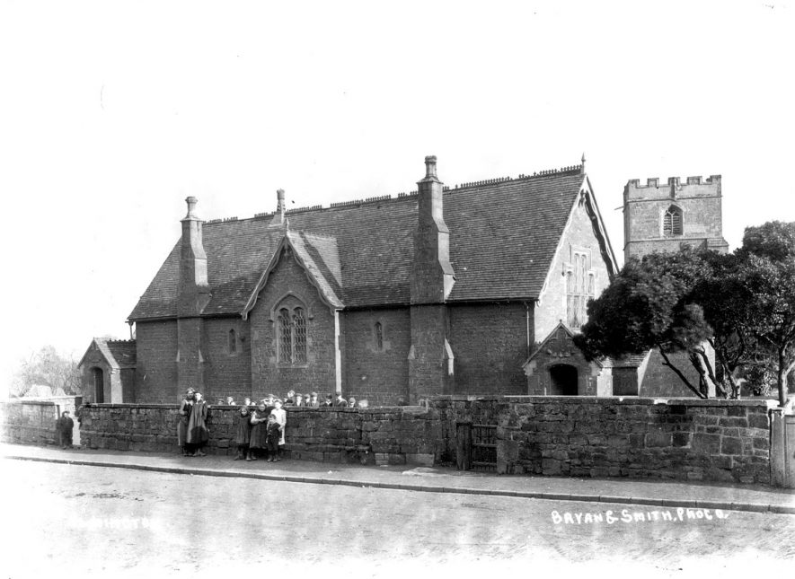 Ilmington village school with pupils standing by wall.  1900s |  IMAGE LOCATION: (Warwickshire County Record Office)