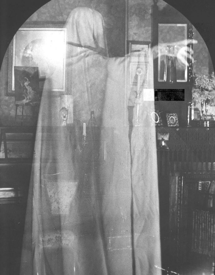 Ghostly figure standing in furnished room in Lower Brailes.  1900s |  IMAGE LOCATION: (Warwickshire Museums. Photographic Collections.)