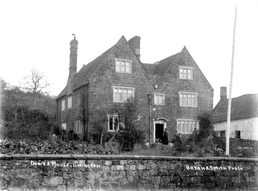Exterior of the Dower House, Ilmington.  A man and woman are standing in the garden.  1900s |  IMAGE LOCATION: (Warwickshire County Record Office)